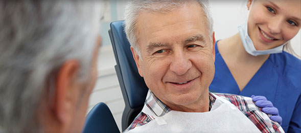 elderly man smiling at dentist