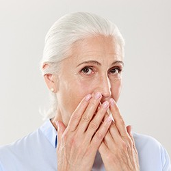 older woman covering mouth embarrassed needs dental implant placement