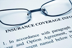 Insurance coverage paperwork with glasses on top