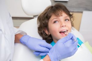 little boy smiling sitting dental chair