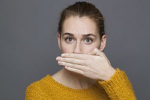 woman covering mouth bad breath