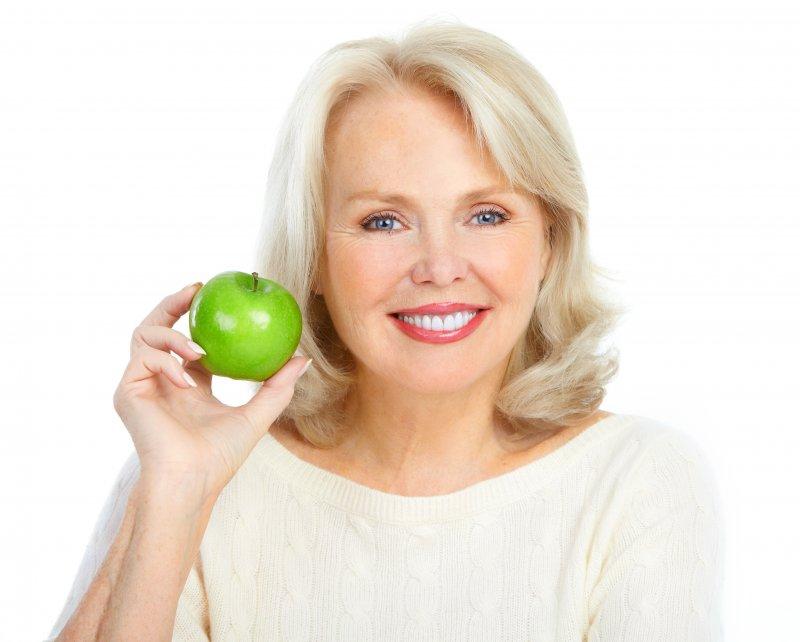 older woman blonde hair holding apple