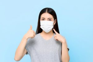 young woman wearing face mask to visit dentist