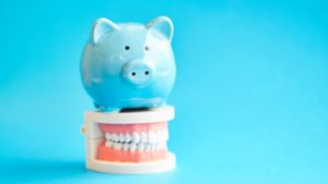 light blue piggy bank sitting atop false teeth against light blue background