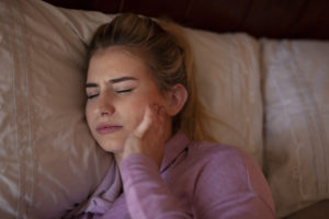 Woman in bed holding jaw in discomfort